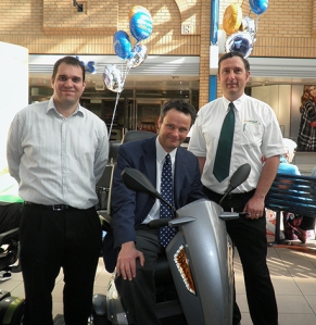 Picture caption:  Peter Aldous, MP for Waveney (centre) rides a TGA Vita mobility scooter whilst supporting Beactive Mobility's Motability event in Lowestoft on 18 September 2012. Peter is pictured with Martyn Simpson, TGA Area Sales Manager (left) and Shaun Green, Beactive Mobility's Motability Manager (right).
